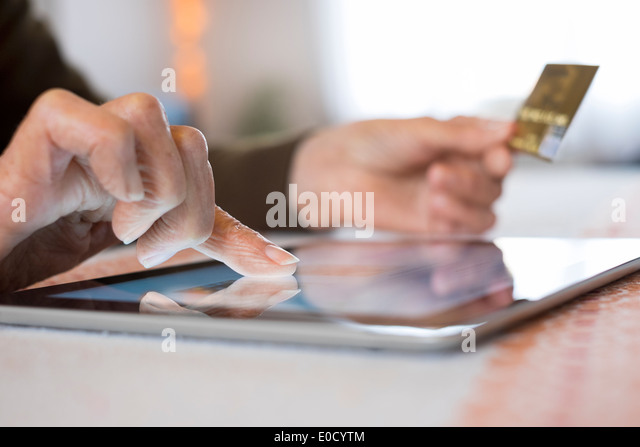 Mature female digital tablet closeup hands plastic card shop indoors - Stock Image