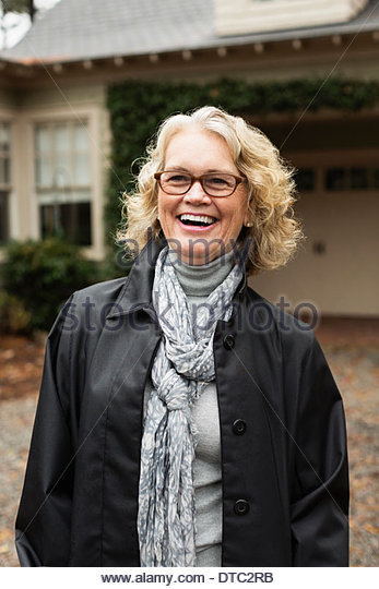 Portrait of contented senior woman outside house - Stock Image