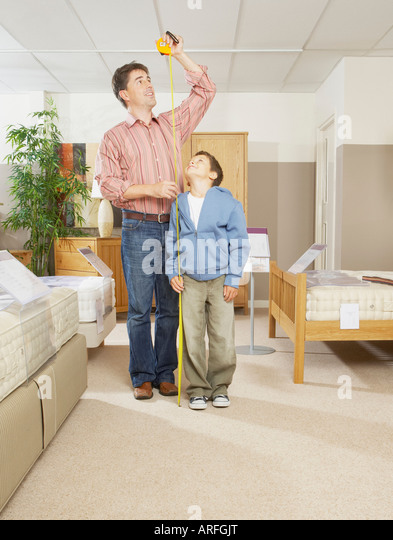 Man and boy measuring each others height - Stock Image