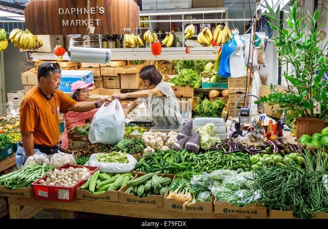 Honolulu Hawaii Hawaiian Oahu Chinatown Kekaulike Street produce covered market Asian woman man sale display buying - Stock Image
