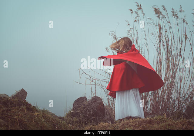 Dark and surreal  portrait of a red hooded woman . Sadness and loneliness conceptual - Stock-Bilder