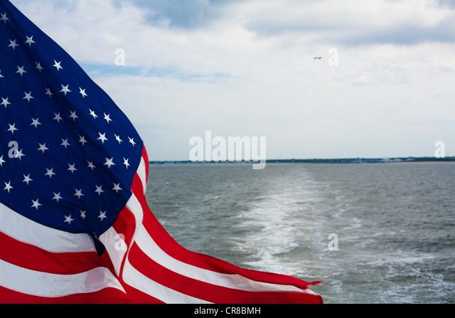 USA flag flying on back of boat - Stock Image