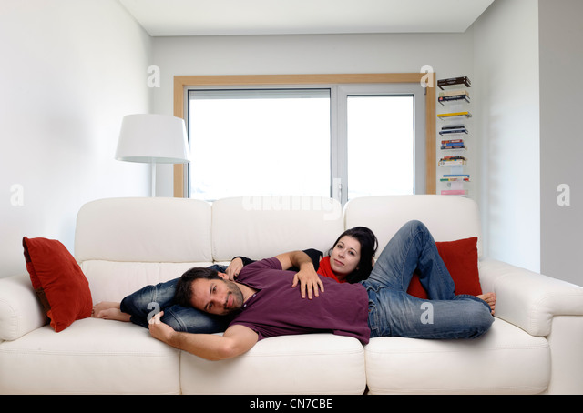 Young couple at home in the living room lying on a white sofa - Stock Image