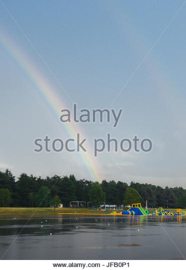 Playground for kids on the water with a rainbow - Stock Image