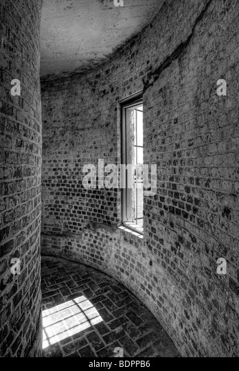 A curved brick corridor with a window - Stock-Bilder