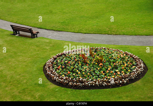 Flower bed and bench at the Parade Gardens, beside the River Avon in the centre of Bath City, Somerset, United Kingdom. - Stock Image
