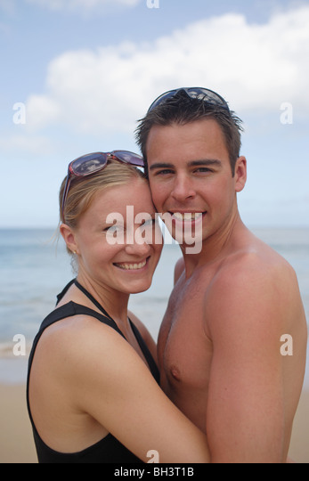 Young couple embracing on beach, smiling - Stock Image
