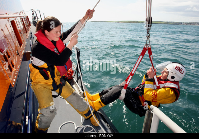 Female RNLI lifeboat volunteer winches a crew man aboard on exercise - Stock Image