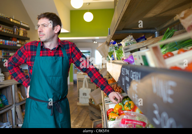 Grocer arranging produce for sale - Stock Image