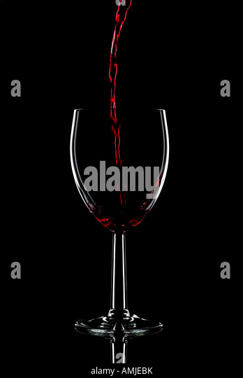 Low key shot of red wine being poured into a glass against a black background - Stock-Bilder