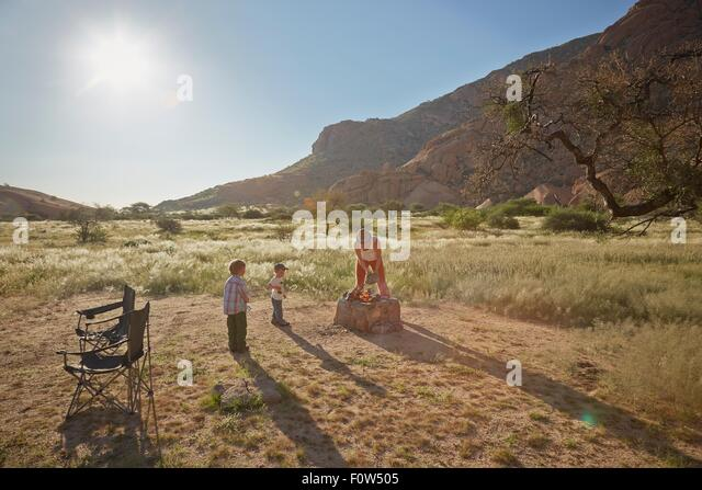 Mother cooking food on campfire while children watch, Swakopmund, Erongo, Namibia - Stock Image