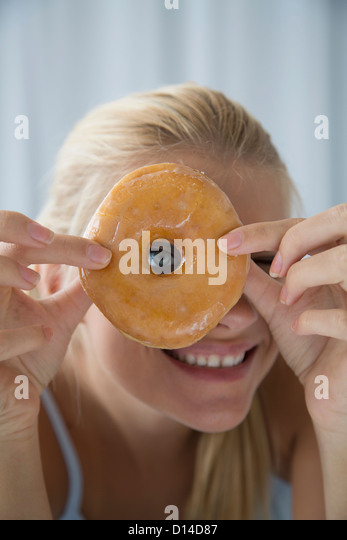 Woman peering through donut hole - Stock Image