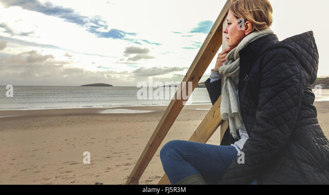 young woman sitting on wooden stairs on the beach - Stock-Bilder