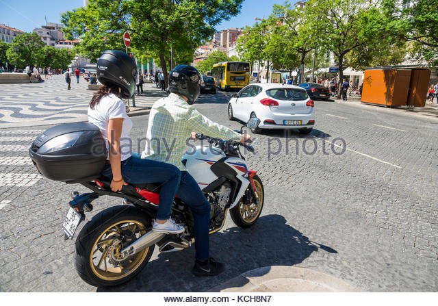 Lisbon Portugal historic center Rossio Square Praca Rossio traffic motorcycle couple man woman helmet stop - Stock Image