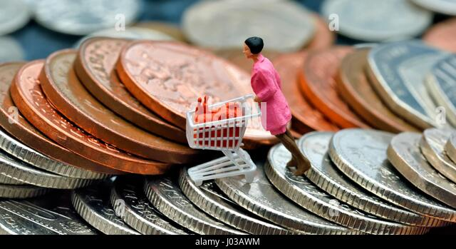 Woman pushing shopping trolley - Stock Image