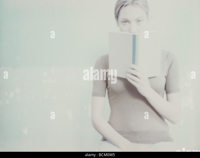 Woman looking at camera over open book - Stock Image