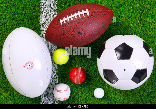 Photo of various sports balls on a grass next to the white line, shot from above. - Stock Image