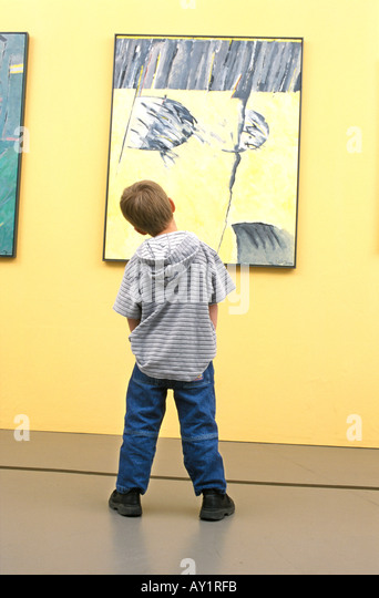 Boy in front of an abstract painting - Stock Image
