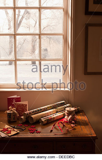 Christmas wrapping paper, ribbon, gift and cards near window - Stock Image