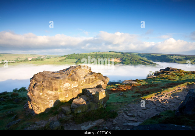 Low lying mist in the valley below Froggatt Edge, a gritstone escarpment, at dawn in the Peak District National - Stock Image