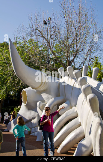 Fivels Playland kids playground with family standing beside huge cow skeleton at Universal Studios Orlando Florida - Stock Image