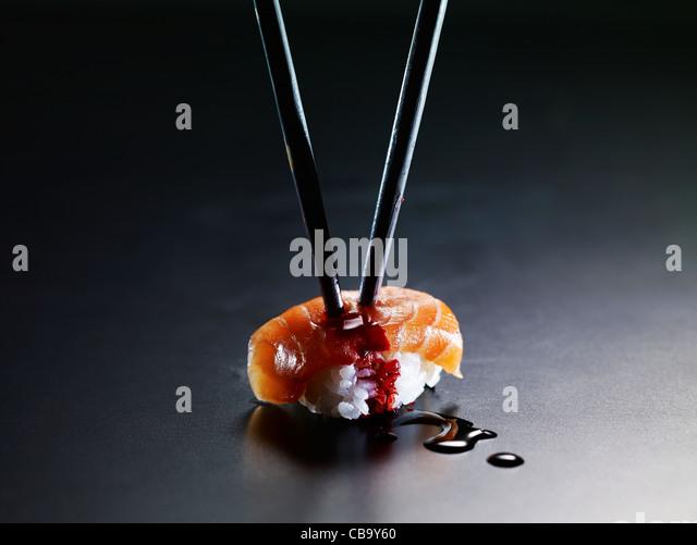 Sushi impaled by chopsticks - Stock Image