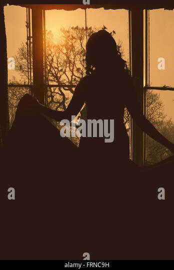 silhouette of the back of young woman holding her dress standing by the large window - Stock Image