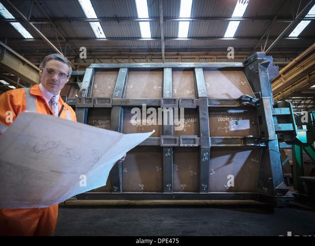 Engineer inspecting engineering drawings in factory - Stock-Bilder