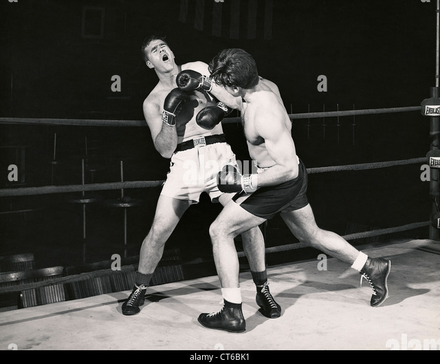 Boxer throws punches at opponent against the rings - Stock Image