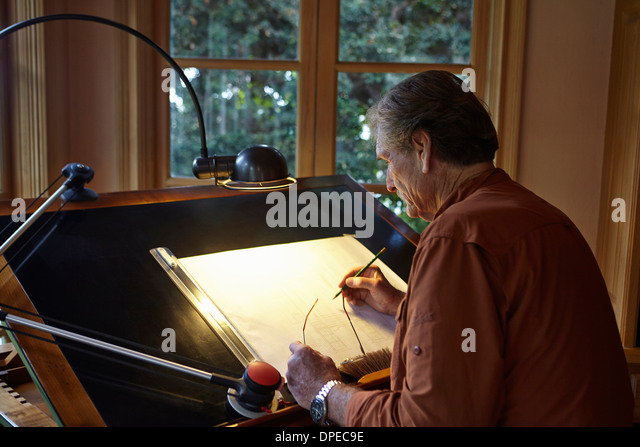 Senior man working on architectural drawing at home - Stock-Bilder