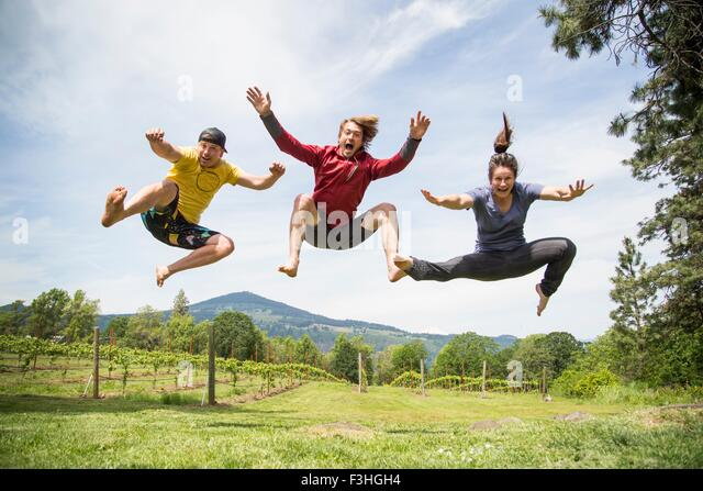 Three adults jumping in rural setting, mid air, laughing - Stock Image