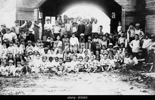 Full length landscape shot of schoolchildren seated and standing in rows outdoors, some African American, all wearing - Stock Image