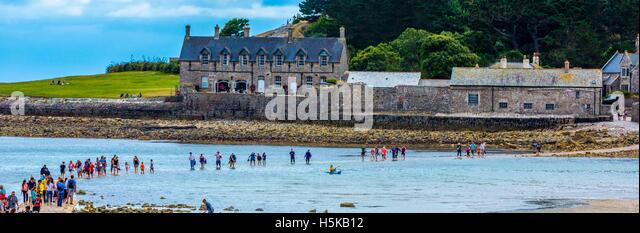 a  view of people being overwhelmed on the causeway by the incoming tide a St. Michael's Bay and sea shore in - Stock Image