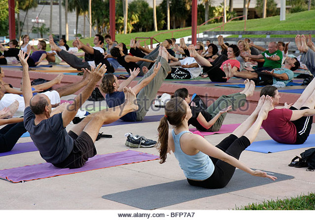 Miami Florida Bayfront Park yoga class group dog stretch exercise fitness man woman health - Stock Image