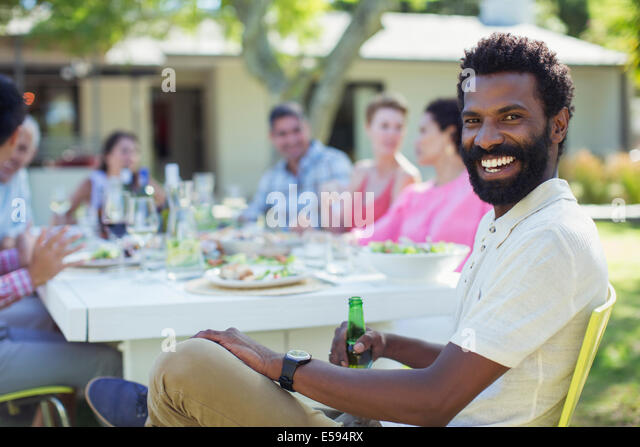 Man smiling at table outdoors - Stock Image