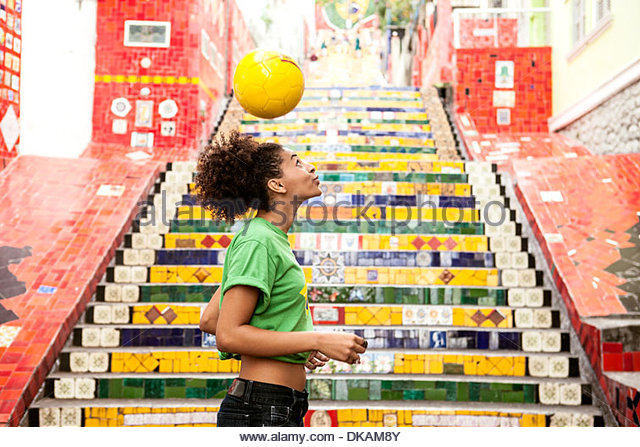 Young woman doing keepy uppys in front of the Escadaria Selaron steps in Rio de Janiero, Brazil - Stock Image