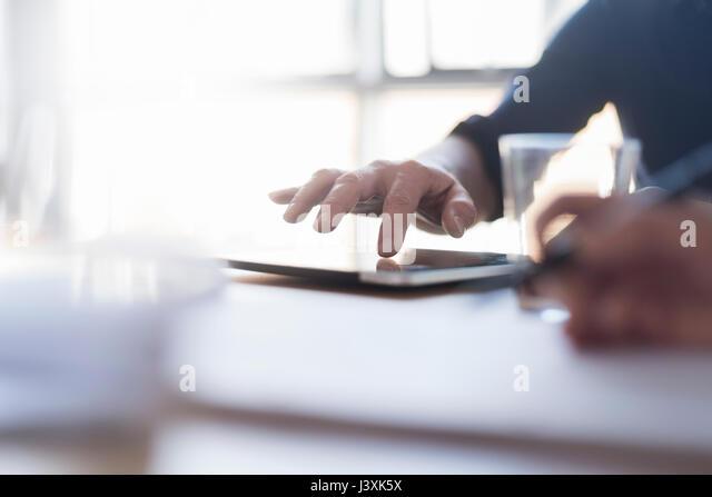 Man using digital tablet on desk, close up of hand - Stock Image