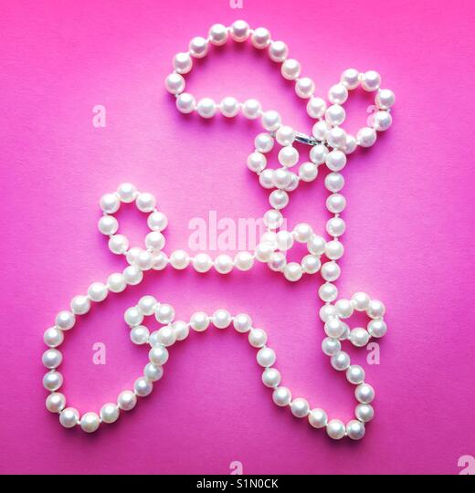 A bright close-up shot of a string of pearls on a pink background made to look like an animal shape - Stock Image