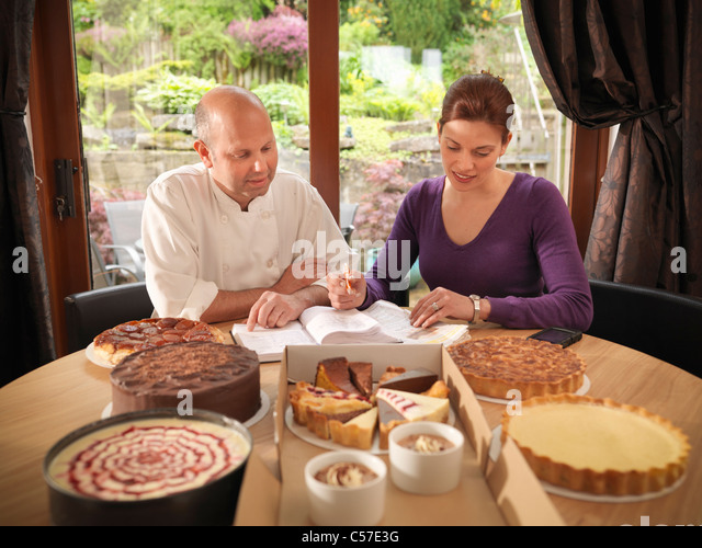 Pastry chef working with customer - Stock Image