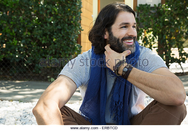 Smiling man with beard and scarf looking away - Stock Image