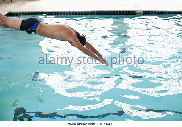 Man diving into swimming pool - Stock Image