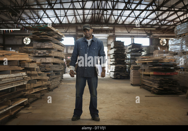 A heap of recycled reclaimed timber planks of wood reclamation in a timber yard A man in work overalls with a clipboard - Stock Image