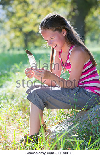 Smiling girl, looking at feather, sitting in treelined field - Stock Image