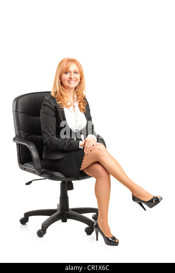 A portrait of a smiling businesswoman sitting on a chair isolated on white background - Stock Image