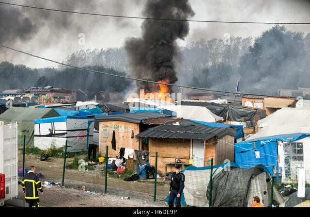 Chaotic scenes in the Calais Jungle after dozens of fires were set leading to a series of explosions shortly before - Stock-Bilder