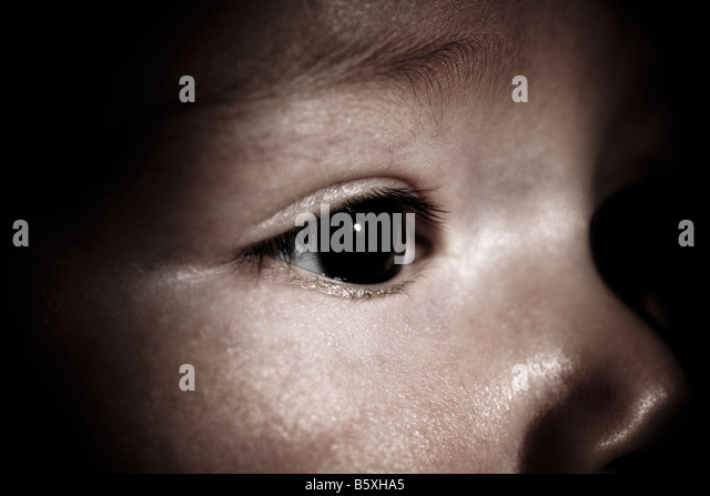 five 5 months old baby boy eurasian mix but looks caucasian close up with dramatic lighting - Stock Image