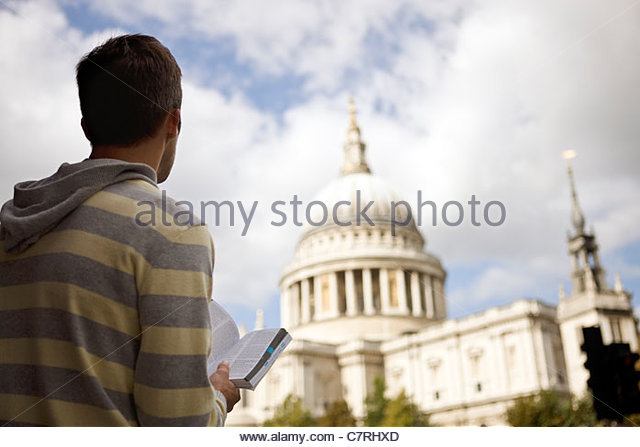 A mid-adult man standing in front of St Paul's cathedral, looking at a guidebook - Stock Image