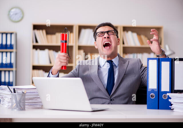 Businessman with dynamite in the office - Stock Image