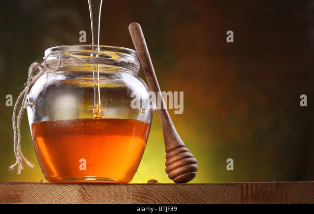 Pot is being filled with honey and a drizzler. Oblects are on wooden table. - Stock Image