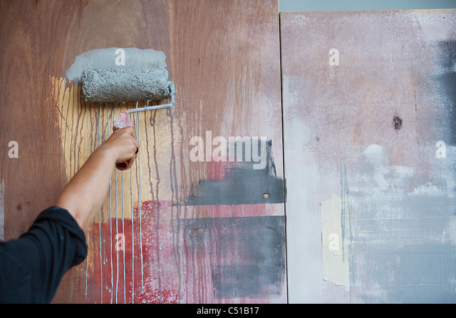 detail of woman painting wall - Stock Image